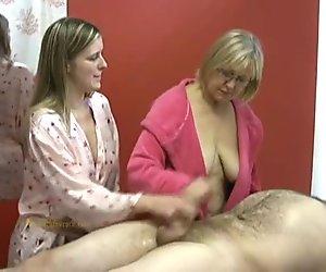 Senior masseuse helps junior masseuse in jerking off a naked clie